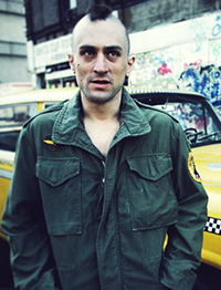 Photo from the movie Taxi Driver showing actor Robert De Niro portraying psycho killer Travis Bickle. In this photo Bickle is wearing an Army jacket and his hair is cut in a Mohawk.