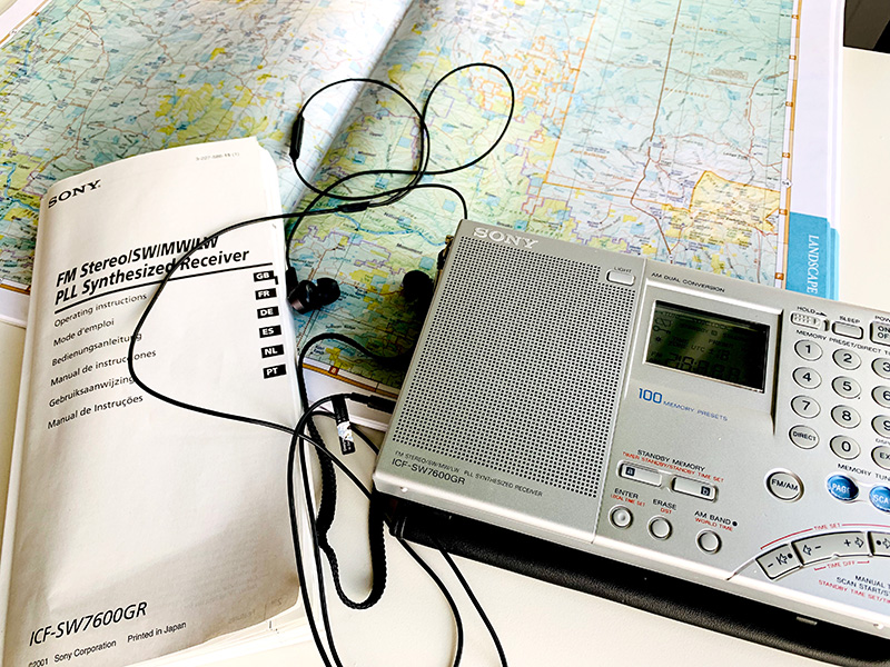 Photo of a Sony ICF-SW7600GR shortwave radio on a table. Next to the paperback book size radio are its instruction book, earbud headphones and a map.