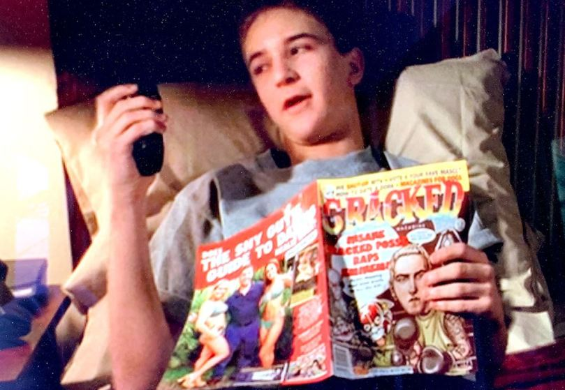 Framegrab from Stargate SG-1 episode Fragile Balance of actor Michael Welch portraying a teenage clone of Richard Dean Anderson. Welch is holding a copy of Cracked magazine, which can be said to be a younger version of Mad magazine.