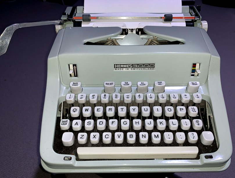 Photo shows a Hermes 3000 typewriter. The machine is a later model from probably the mid-1960s. It's minty green in color and unlike previous smooth-curve models, has a somewhat more angular design.