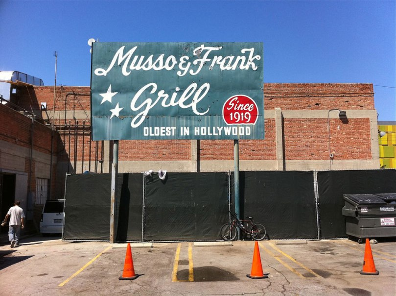 Photo taken of a large sign for Musso & Frank Grill in Hollywood on a bright sunny day. The dark green sign features the restaurant's name in white cursive lettering.