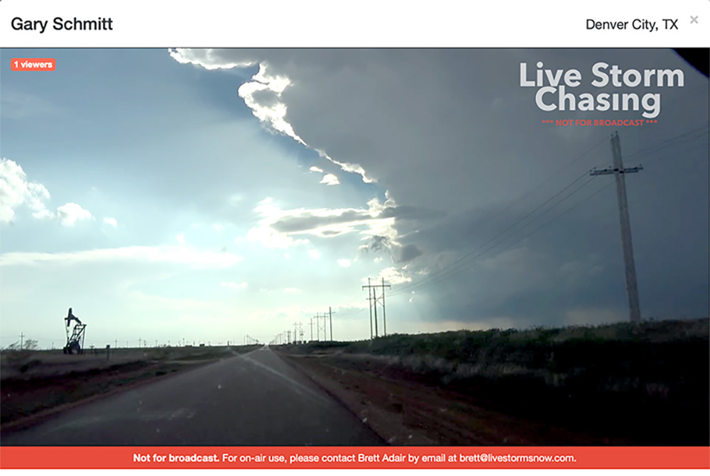 Screenshot from a live video feed at Live Storm Chasers. It shows a view of Texas flatlands as a gray thunderstorm brews on the horizon.