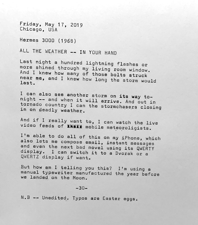 This photo is of a typewritten page with the following text. Friday, May 17, 2019. Chicago, USA. Hermes 3000. All the weather — right in your hand. Last night a hundred lightning flashes or more shined through my living room window. And I knew how many of those bolts struck near me, and I knew how long the storm would last. I can also see another storm on its way to— night — and when it will arrive. And out in tornado country I can the stormchasers closing in on deadly weather. And if I really want to, I can watch the live video feeds of mobile meteorologists. I'm able to do all of this on my iPhone, which also lets me compose email, instant messages and even the next bad novel using its QWERTY display. I can switch it to a Dvorak or a QWERTZ display if want. But how am I telling you this? I'm using a manual typewriter manufactured the year before we landed on the Moon. Note: This typecast is unedited. Typos are Easter eggs.