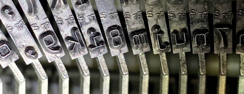 Close-up view of typewriter type slugs that show insignias of the letters S and TP.