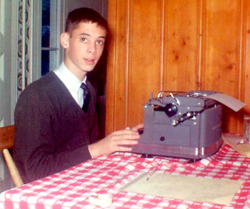 A young John Waters sits at a typewriter in what appears to be a table in a home's kitchen.