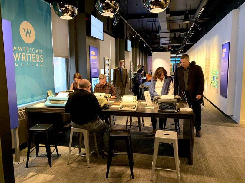 Photo of several people using some of the eight typewriters available for visitors to try out at the American Writers Museum in Chicago.