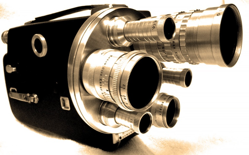 Photo of a 1950s-era Cine-Kodak K-100 turret movie camera. This 16mm camera has three lenses on front and a leather-and-polished aluminum body.