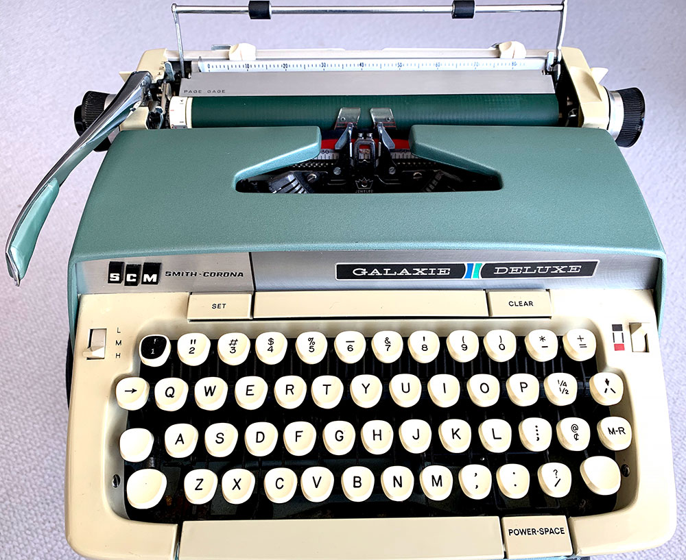 Photo of a beautiful SCM Smith-Corona Galaxie Deluxe typewriter manufactured in 1967. The machine's exterior is painted in colors associated with the era. In this case, a greenish-blue color called seafoam green complemented by creamy beige accents.