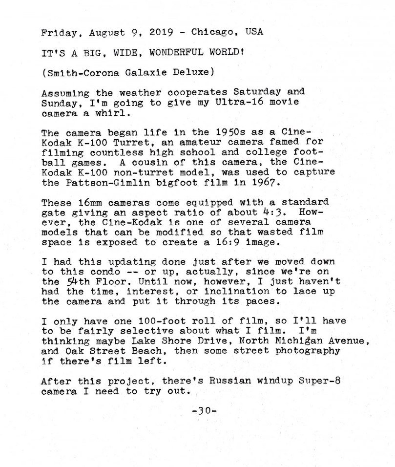 Photo of a typewritten sheet of paper with the following text. Friday, August 9, 2019. Chicago, USA. It's a big, wide, wonderful world! Smith-Corona Galaxie Deluxe. Assuming the weather cooperates Saturday and Sunday, I'm going to give my Ultra-16 movie camera a whirl. The camera began life in the 1950s as a Cine-Kodak K-100 Turret, an amateur camera famed for filming countless high school and college football games. A cousin of this camera, the CineKodak K-100 non-turret model, was used to capture the Patterson—Gim1in bigfoot film in 1967. These 16mm cameras come equipped with a standard gate giving an aspect ratio of about 4:3. However, the Cine—Kodak Is one of several camera models that can be modified so that wasted film space is exposed to create a 16:9 image. I had this updating done just after we moved down to this condo — or up, actually, since we're on the 54th Floor. Until now, however, I just haven't had the time, interest, or inclination to lace up the camera and put it through its paces. I only have one 100—foot roll of film, so I'll have to be fairly selective about what I film. I'm thinking maybe Lake Shore Drive, North Michigan Avenue, and Oak Street Beach, then some street photography if there's film left. After this project, there's Russian windup Super-8 camera I need to try out.