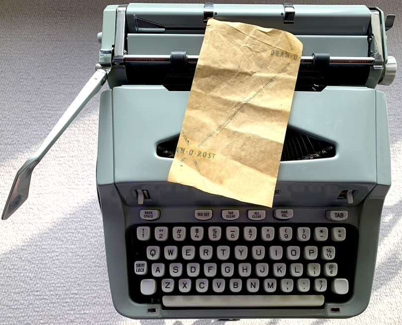 Photo of a 4-by-7-inch piece of brown paper lying on top of a Hermes 3000 semi-squaretop typewriter. The piece of paper has the brand name Bran-O-Rost printed on it. This specially coated paper was found inside the typewriter and might have been there to prevent rust.