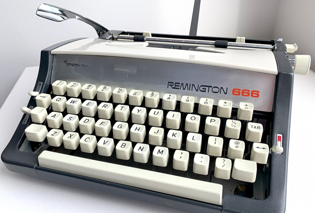 Photo shows a small, manual typewriter painted gray and white. The faceplate reads Sperry Rand Remington 666. There is a rectangular blemish on the nameplate where a sticker has been removed.